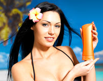 Woman on the beach  holds orange sun tan lotion bottle. Stock Images