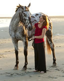 Woman on the beach with horse. Woman with her appaloosa horse on the beach Stock Photo