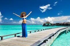 Woman on a beach jetty at Maldives Stock Photo