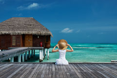 Woman on a beach jetty at Maldives Stock Photo