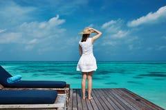 Woman on a beach jetty at Maldives Stock Image