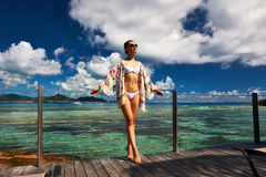 Woman on a beach jetty at Seychelles, La Digue. Stock Photos