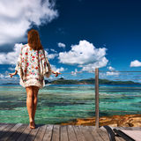 Woman on a beach jetty at Seychelles, La Digue. Stock Photo