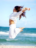 Woman at the beach jumping Royalty Free Stock Photo
