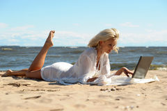 Woman at a beach with a laptop. Happy blonde woman at a beach with a laptop Stock Images