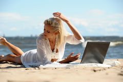 Woman at a beach with a laptop. Happy blonde woman at a beach with a laptop Royalty Free Stock Images