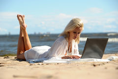 Woman at a beach with a laptop. Happy blonde woman at a beach with a laptop Stock Image