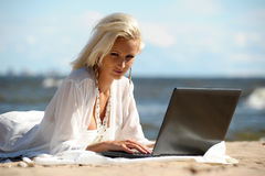 Woman at a beach with a laptop. Happy blonde woman at a beach with a laptop stock photo