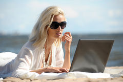Woman at a beach with a laptop. Happy blonde woman at a beach with a laptop Stock Photography