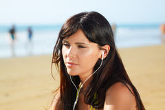 Woman on the beach  listening to music Royalty Free Stock Photo