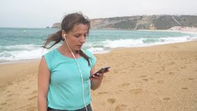 Woman on beach listening to music on headphones from smart phone. Nazare, Portugal. Slow motion stock footage