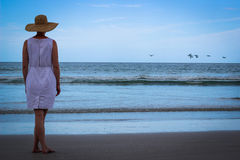 Woman On Beach Looking At Ocean With Birds Flying. Woman in white dress standing on beach with birds flying in background Royalty Free Stock Photos