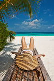 Woman at beach lying on chaise lounge. Woman at beautiful beach lying on chaise lounge stock image