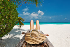 Woman at beach lying on chaise lounge. Woman at beautiful beach lying on chaise lounge stock photography