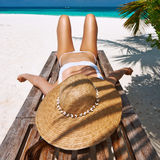 Woman at beach lying on chaise lounge Royalty Free Stock Photos