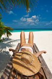 Woman at beach lying on chaise lounge Royalty Free Stock Images