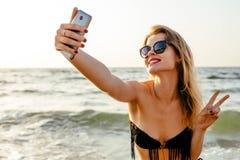 Woman on beach making self portrait Royalty Free Stock Photos