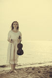 Woman on beach near sea holding violin Royalty Free Stock Photography