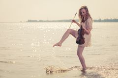 Woman on beach near sea holding violin Stock Images
