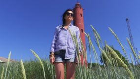 Woman on the beach at the old lighthouse. In summer day stock video footage