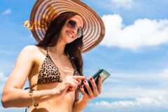Woman on beach with phone chatting Royalty Free Stock Images