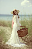 Woman at the beach with picnic basket Royalty Free Stock Images