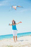 Woman on beach playing with a colorful kite Stock Images