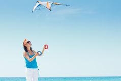 Woman on beach playing with a colorful kite Royalty Free Stock Images