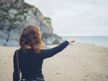 Woman at the beach pointing at the sea. A young woman is standing on the beach and is pointing at the sea Royalty Free Stock Image