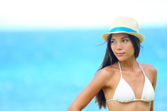 Woman beach portrait looking to side. With wearing hat and beachwear bikini. Beautiful young modern multiracial female model looking serious with subtle smile Stock Image