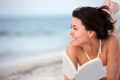 Woman at the beach reading Stock Images