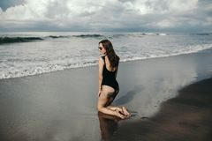 Fashion shot of rear view of beautiful girl with sandy in black swimsuit and sunglasses posing on the beach with royalty free stock photography