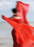 Woman on a beach with red fabric Stock Images