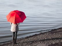 Woman on the beach with a red umbrella. Royalty Free Stock Photo