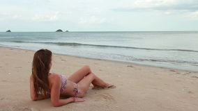 Woman on the beach relaxing near sea stock video