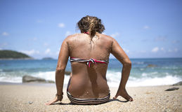 Woman on a beach with sand on her back. Adult Caucasian woman in striped bikini with back turned to camera is sitting on a beach with sand covering her shoulders Royalty Free Stock Photos