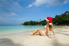 Woman on the Beach with Santa Claus Hat. Celebrating Christmas and New Year in Hot Country Royalty Free Stock Photography