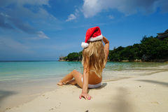 Woman on the Beach with Santa Claus Hat. Celebrating Christmas and New Year in Hot Country
