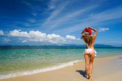 Woman on the Beach with Santa Claus Hat. Celebrating Christmas and New Year in Hot Country Royalty Free Stock Photos