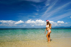 Woman on the Beach with Santa Claus Hat. Celebrating Christmas and New Year in Hot Country Royalty Free Stock Photo