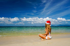 Woman on the Beach with Santa Claus Hat. Celebrating Christmas and New Year in Hot Country Royalty Free Stock Image