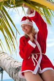 Woman on the beach in santa's costume Stock Photo
