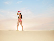 Woman on the beach in santa's hat Stock Photos