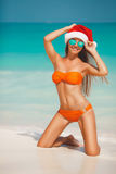 Woman on the beach in santa's hat Stock Photography