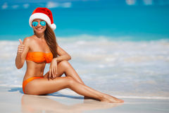 Woman on the beach in santa's hat. Young woman in santa hat on tropical beach. Christmas vacation. Christmas beach vacation travel woman wearing Santa hat and Royalty Free Stock Image