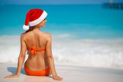 Woman on the beach in santa's hat Stock Image