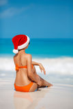 Woman on the beach in santa's hat Stock Photo