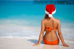 Woman on the beach in santa's hat Stock Photos
