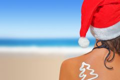 Woman on the beach in santas hat Royalty Free Stock Images