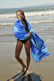 Woman on beach with sarong wrapped around her. Woman in sarong n beach smiling Royalty Free Stock Image